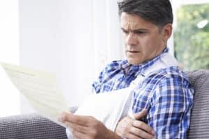 Injured Man Reading Medical Bills in Detroit, MI