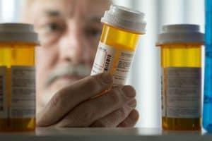 Senior reading the warning label on dangerous prescription drugs