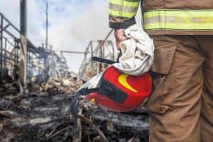 Firefighter standing over remains of gas explosion.