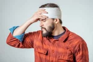 Portrait of injured man with bandaged wrapped due to a brain injury