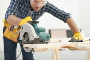 Carpenter working with circular saw. Over time this can lead to a repetitive stress injury