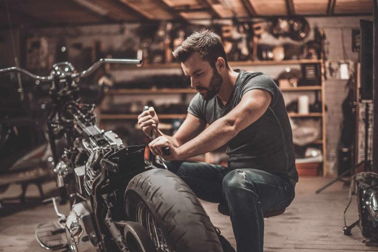 Rider modifying his bike with aftermarket parts