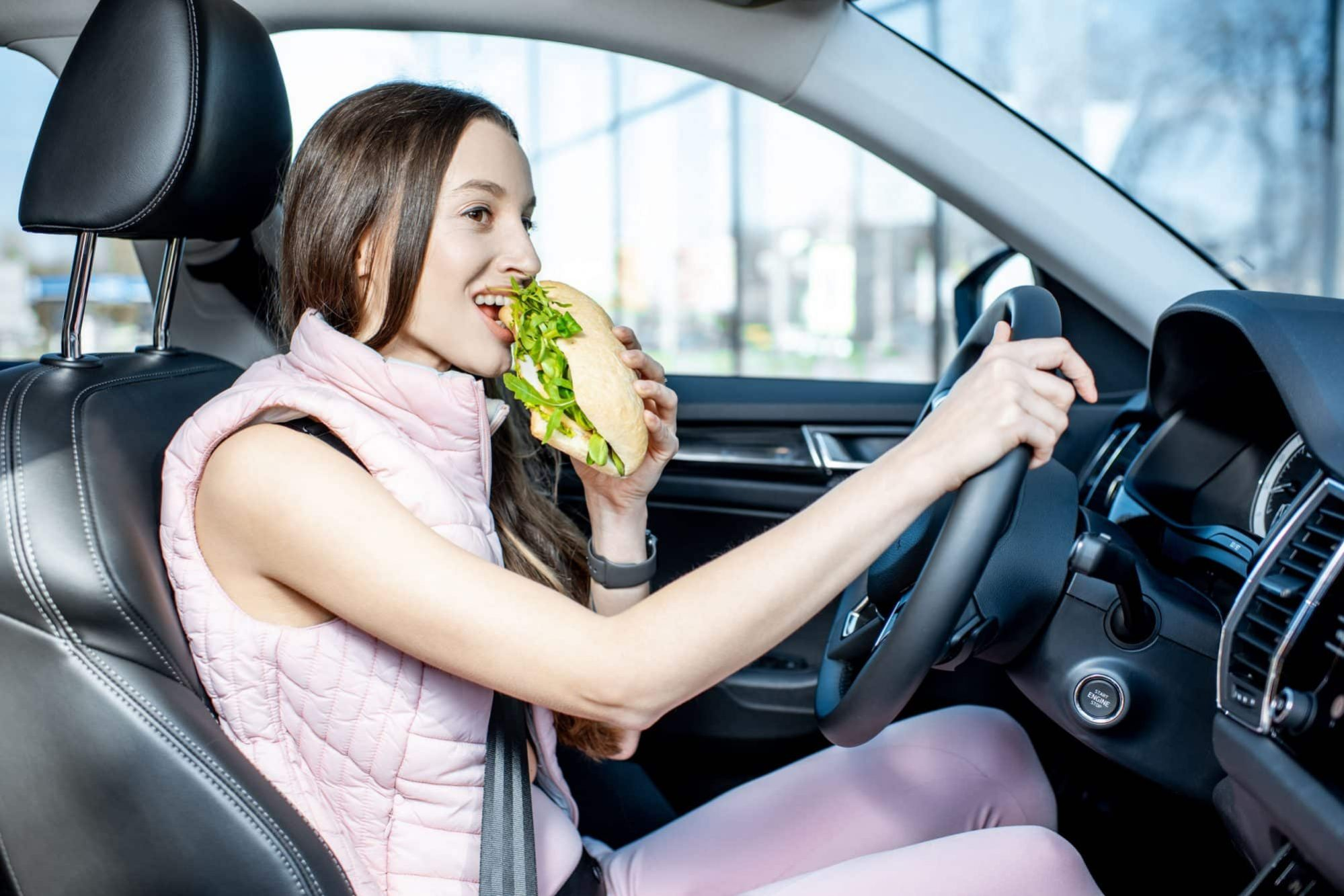 Young woman in Michigan eating while driving a vehicle