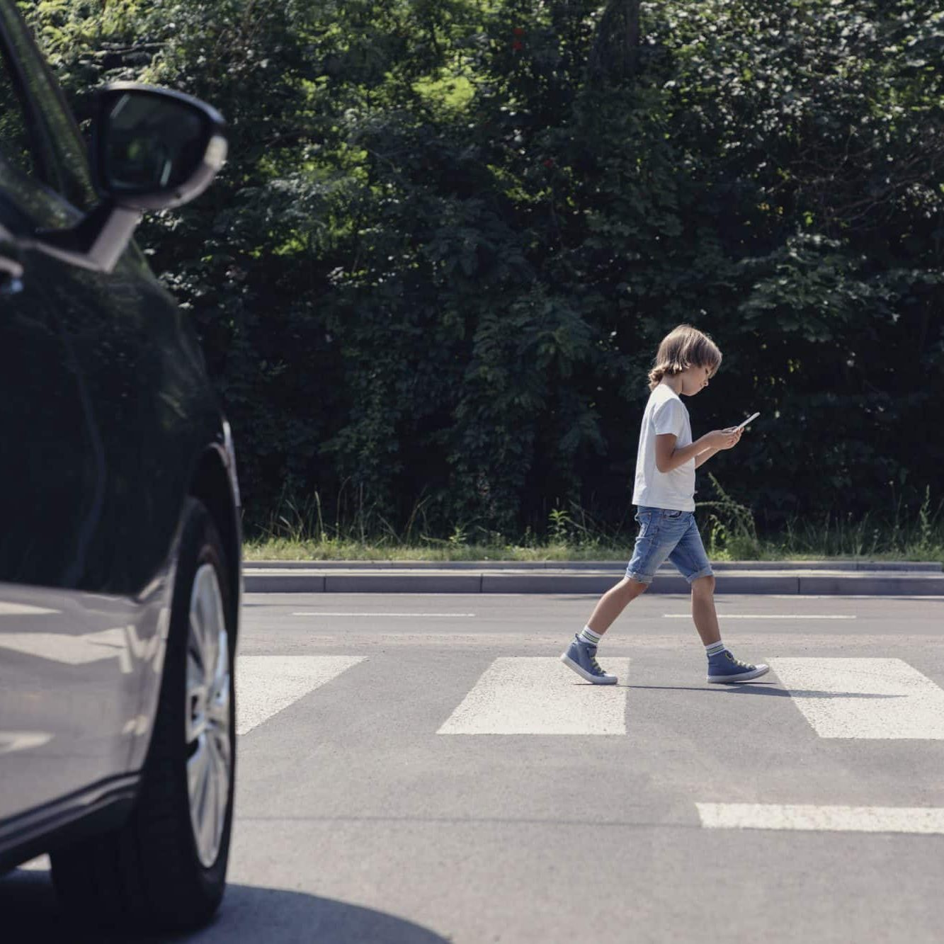 Child crossing the street while looking at smart phone
