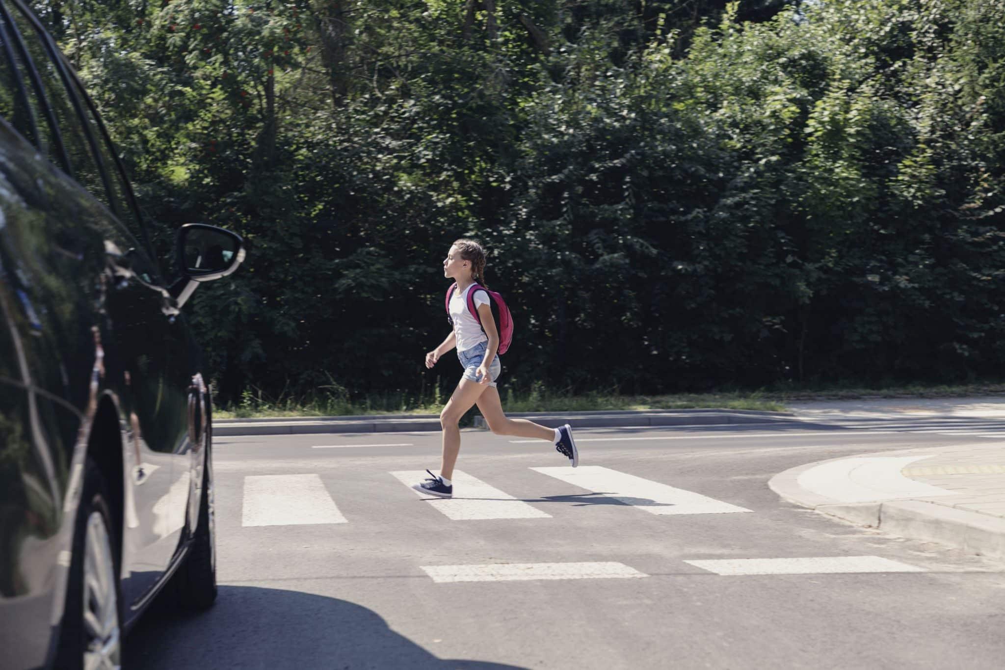 Girl pedestrian walking through a crosswalk