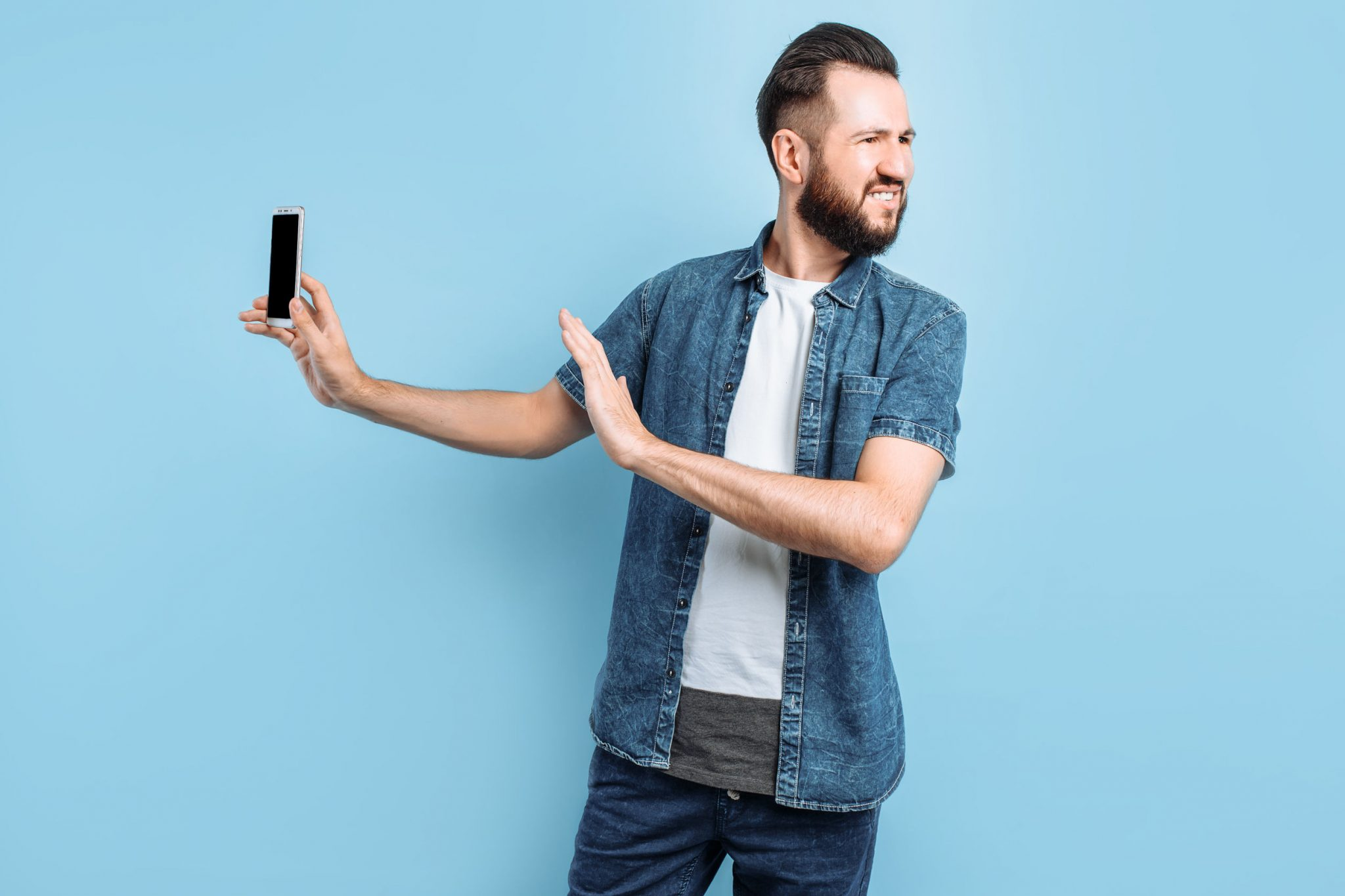 An irritated young man keeps his smartphone away from his ear. An angry person does not want to listen to a conversation on the phone, standing on an isolated blue background