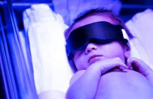 Newborn infant baby boy receiving phototherapy for jaundice at the hospital because of Caput Succedaneum