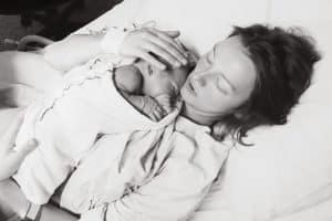Mother holding her newborn baby after labor in a hospital.