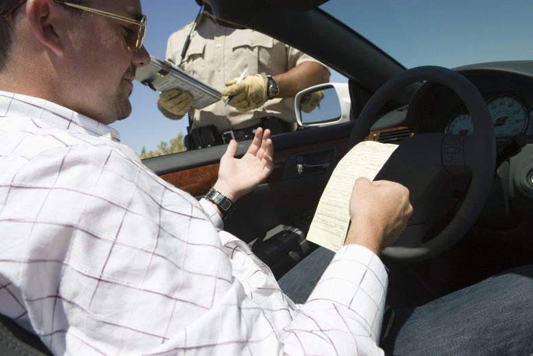 Police officer giving driver a ticket for not providing insurance information