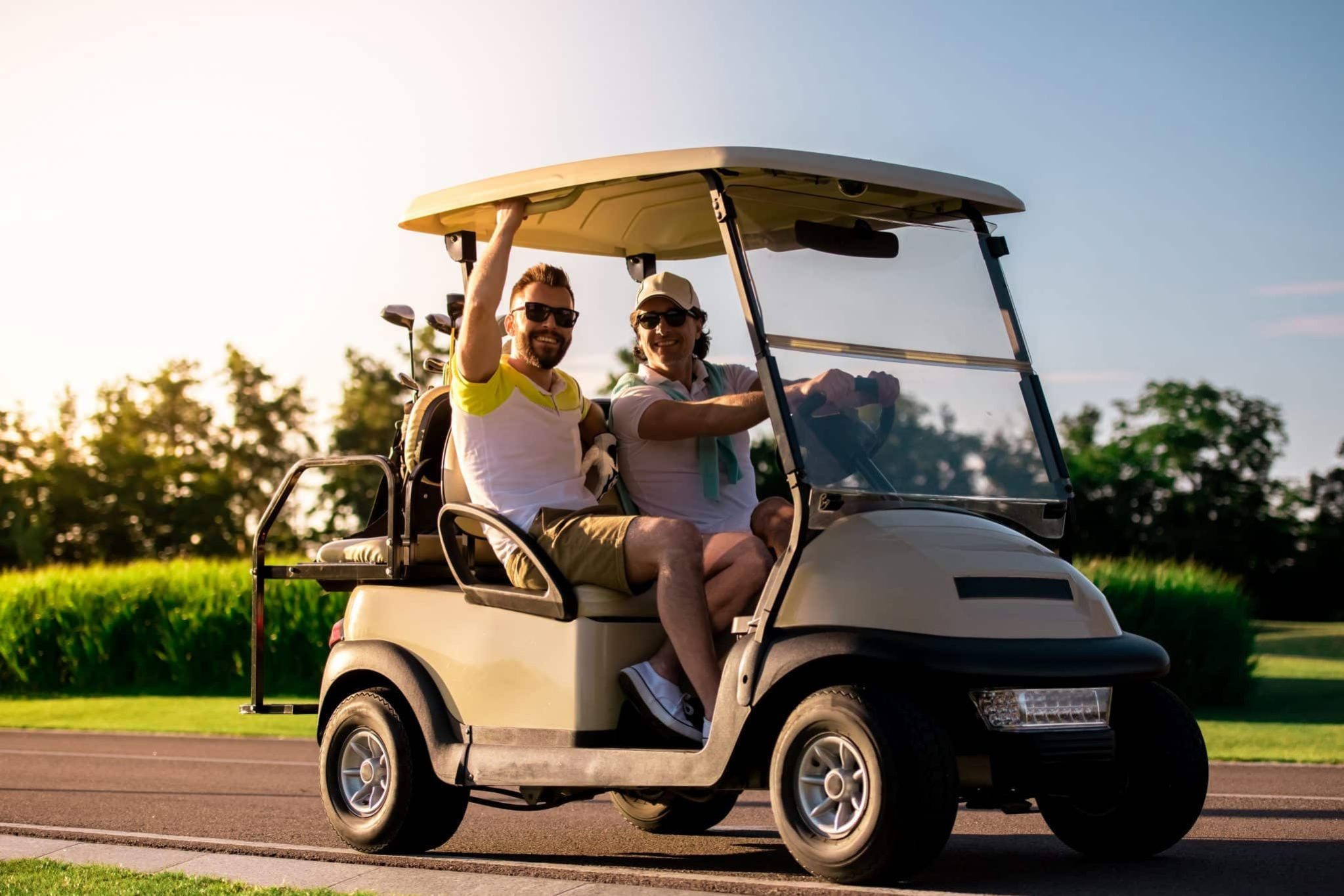 Handsome men are looking at camera and smiling while driving a golf cart and searching for a golf hole